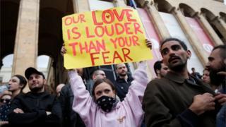 """""""Nuestro amor suena más fuerte que tu miedo"""", dice el cartel de una manifestante frente al Parlamento de Georgia el pasado 12 de mayo."""