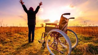 Mujer que se levanta de una silla de ruedas