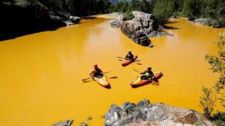 People kayak in the Animas River near Durango, Colorado, on 6 August in water coloured from a mine waste spill.
