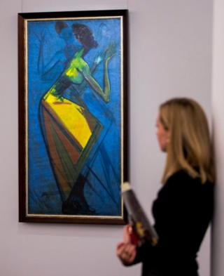Ben Enwonwu's painting Africa Dances is seen on a wall. A woman is seen, out-of-focus, looking at the piece.