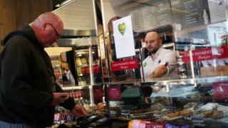 An employee is seen behind a protective screen as they serve a customer in a Pret a Manger store that has reopened for delivery and takeaway in Wimbledon on 1 May