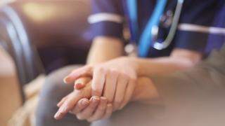 A nurse comforts a patient