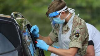 man in army uniform wearing mask, gloves and visor doing swab through car window