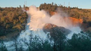 In this handout provided by the California Department of Water Resources (pixel.water.ca.gov), The heavy flows from the 3,000-foot main Oroville dam spillway continues to push debris into the turbid Feather River as the concrete span further eroded and the jagged fracture in its midsection sends water flowing over an adjacent hillside February 11, 2017 in Oroville, California.