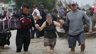 A woman is led through flood waters to safety after Hurricane Harvey