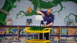 Site manager Mark Lee fills bottles of hand sanitizer at Queen