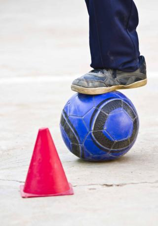 A boy's foot is seen dribbling a football around a cone