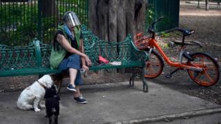 A woman sits in a bench while walking her dogs in Mexico City
