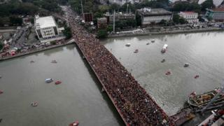 Huge crowds pack the Jones Bridge as the statue passes across it. Manila, Philippines, 9 January 2017.