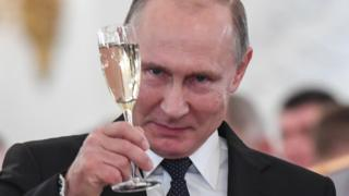 In this file photo taken on December 28, 2017 Russian President Vladimir Putin toasts with attendees after a ceremony to bestow state awards on military personnel who fought in Syria,