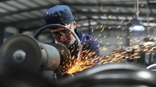 """A worker welds wheel hubs of baby carriages that will be exported at a factory in Hangzhou in China""""s eastern Zhejiang province on June 4, 2018"""
