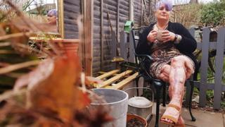 Jayne sentada en su jardín