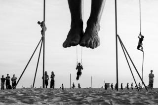 People perform acrobatics on the beach