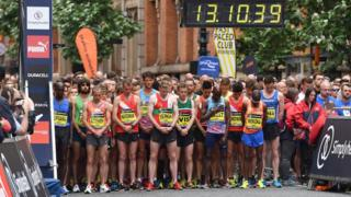 Runners hold a minute's silence