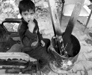 Boy eats a cucumber as he sits next to a fire in eastern Aleppo