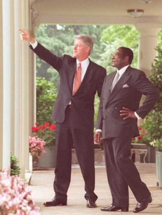 US President Bill Clinton points to items of interest on the White House grounds to President Robert Mugabe, 1995
