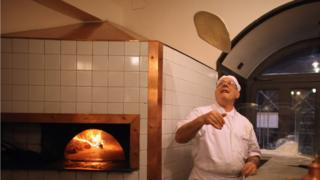 An Italian chef tosses a pizza base in the air in his restaurant kitchen