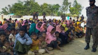Rohingya Muslims from Myanmar who tried to cross the Naf river into Bangladesh are guarded by Bangladeshi security officials in Teknaf on December 25 2016