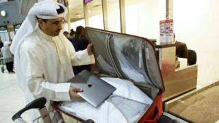 Kuwaiti social media activist Thamer al-Dakheel Bourashed puts his laptop inside his suitcase at Kuwait International Airport in Kuwait City, 23 March