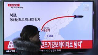 韩国首尔火车站一名女士走过正在播放朝鲜发射导弹报道的电视屏幕(6/3/2017)