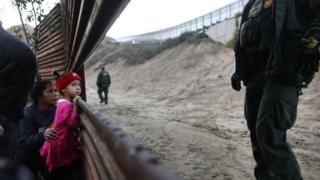Niña migrante en una sección de la valla fronteriza en Tijuana.