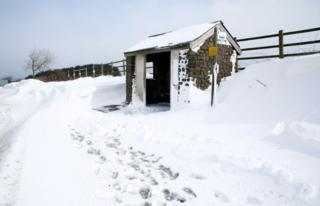 A snowy scene showing a stone bus shelter next to a road
