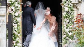The Duchess of Cambridge adjusting Pippa Middleton's dress
