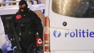 A Belgian special forces police officer patrols a street during a police raid in Brussels, 20 December 2015.