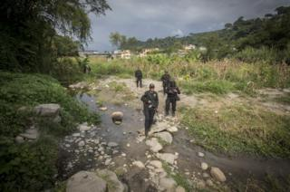 Police officers crossing a stream