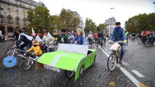 One pickin wey dey ride bicycle wey dey use cardboard take arrange am like car for Place de la Bastille during a 'car free' day.