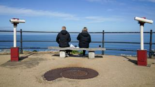 Couple social distancing by the sea