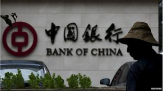 """A man is silhouetted in front of a Bank of China""""s logo at its branch office in Beijing, in this July 14, 2014 file photo"""