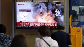 People watch news reports about North Korean shells