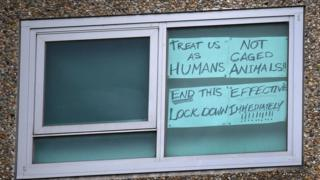 in_pictures A sign in the window of one of the locked-down units reads: Treat as as humans, not as caged animals