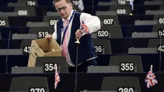 UKIP MEP Raymond Finch puts Union Jack flags on desks in the European Parliament