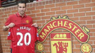 Robin Van Persie holding his Manchester United shirt.