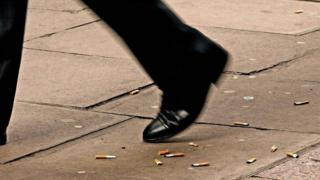 A man walking over discarded cigarette butts