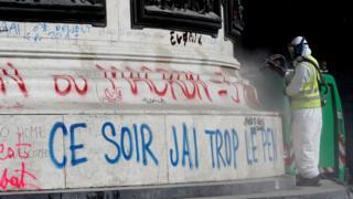 Рабочий удаляет граффити с памятника.