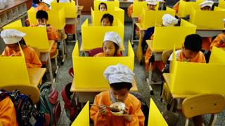 Students eat their lunch on desks with plastic partitions as a preventive measure to curb the spread of coronavirus at a school in Taipei - 29 April 2020