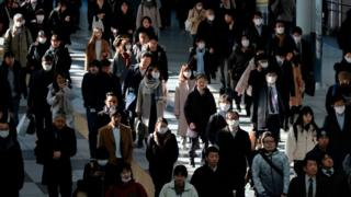 Commuters walk on concourse at a railway's terminal station in Tokyo on January 31, 2020.