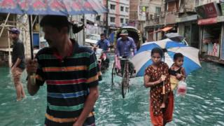 Bangladeshi people walk through waterlogged streets in Bangladesh