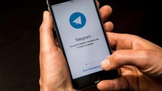 Mobil telefonida Telegram dan foydalanayotgan inson
