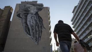 Man in Athens passes mural of praying hands