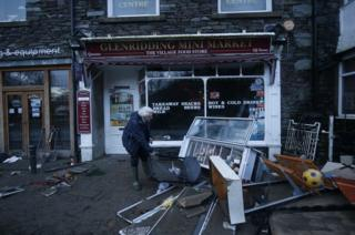 A shopkeeper in Glenridding assesses the damage following the latest flood