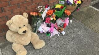 Floral tributes and teddies left outside the apartment block where Sanita Cawley was found injured