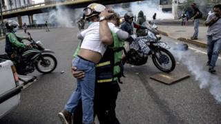 Un rescatista protege a un niño de los gases lacrimógenos.