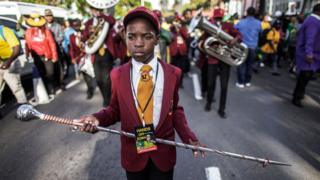 A child leads a brass band on June 8, 2018 outside the High Court, in Durban, as he takes part in a rally in support of former South African president Jacob Zuma.