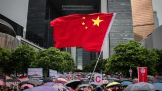 Una bandera china ondea entre un grupo de manifestantes pro gobierno en una manifestación en el parque Tamar, en Hong Kong