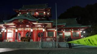 A policeman stands guard in front of the main temple of the Tomioka Hachimangu shrine in Tokyo, Japan in this photo taken by Kyodo on December 8, 2017