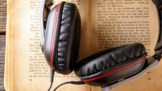 A pair of headphones resting on an open book